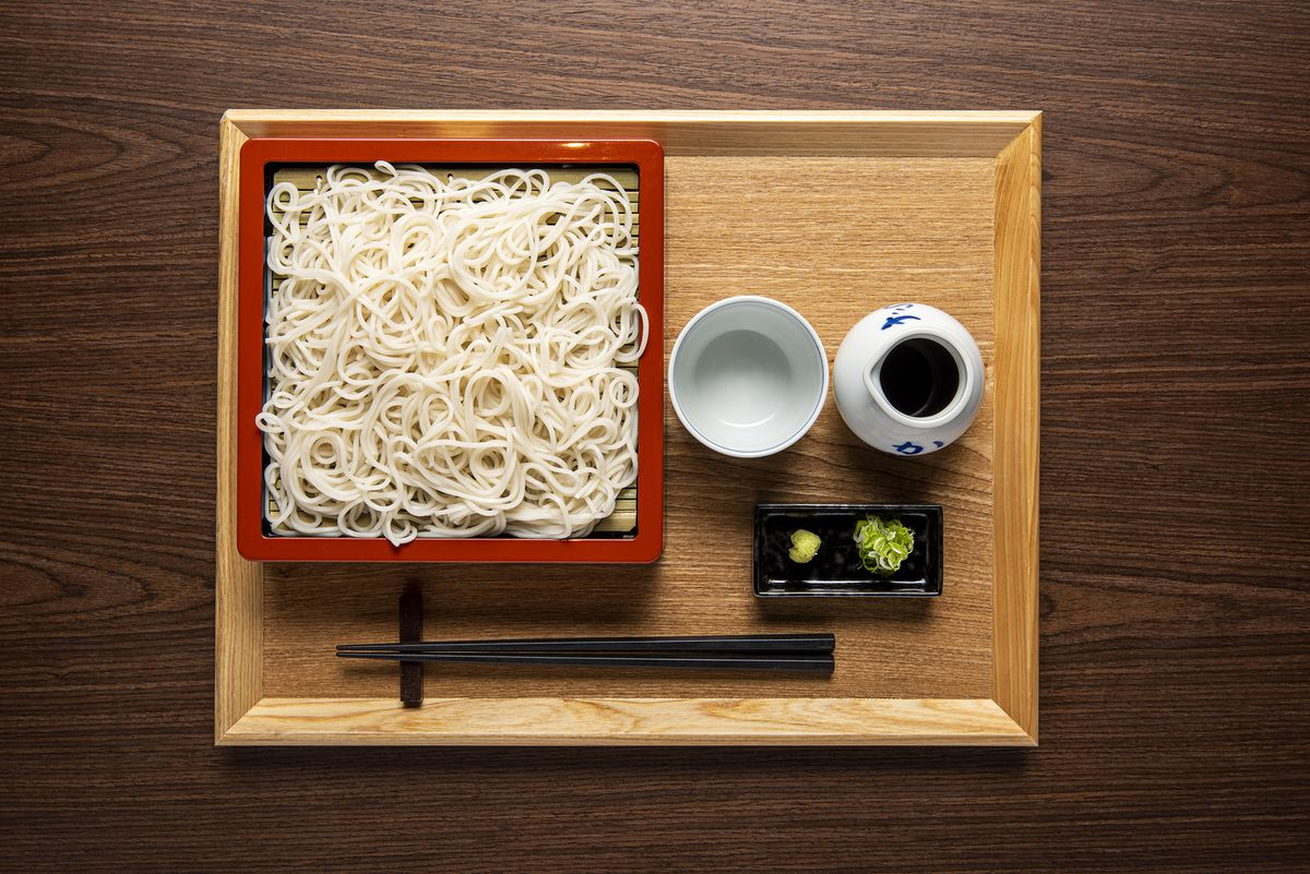 An overhead photograph of a red tray of white noodles, arranged beside a tray of wasabi, ginger, and dipping sauce