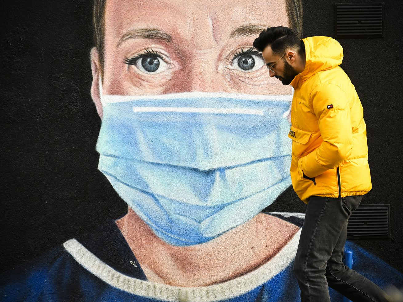 A person walks past a large mural of a face wearing a breathing mask.