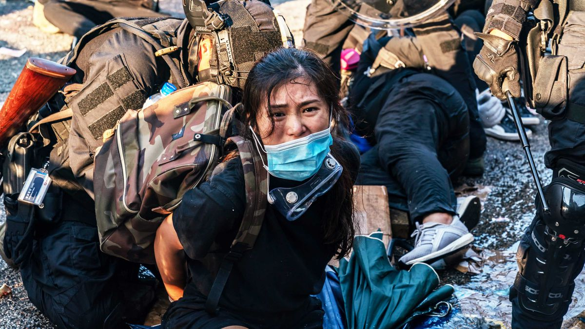 A woman wearing a surgical mask is surrounded by protestors and police officers.