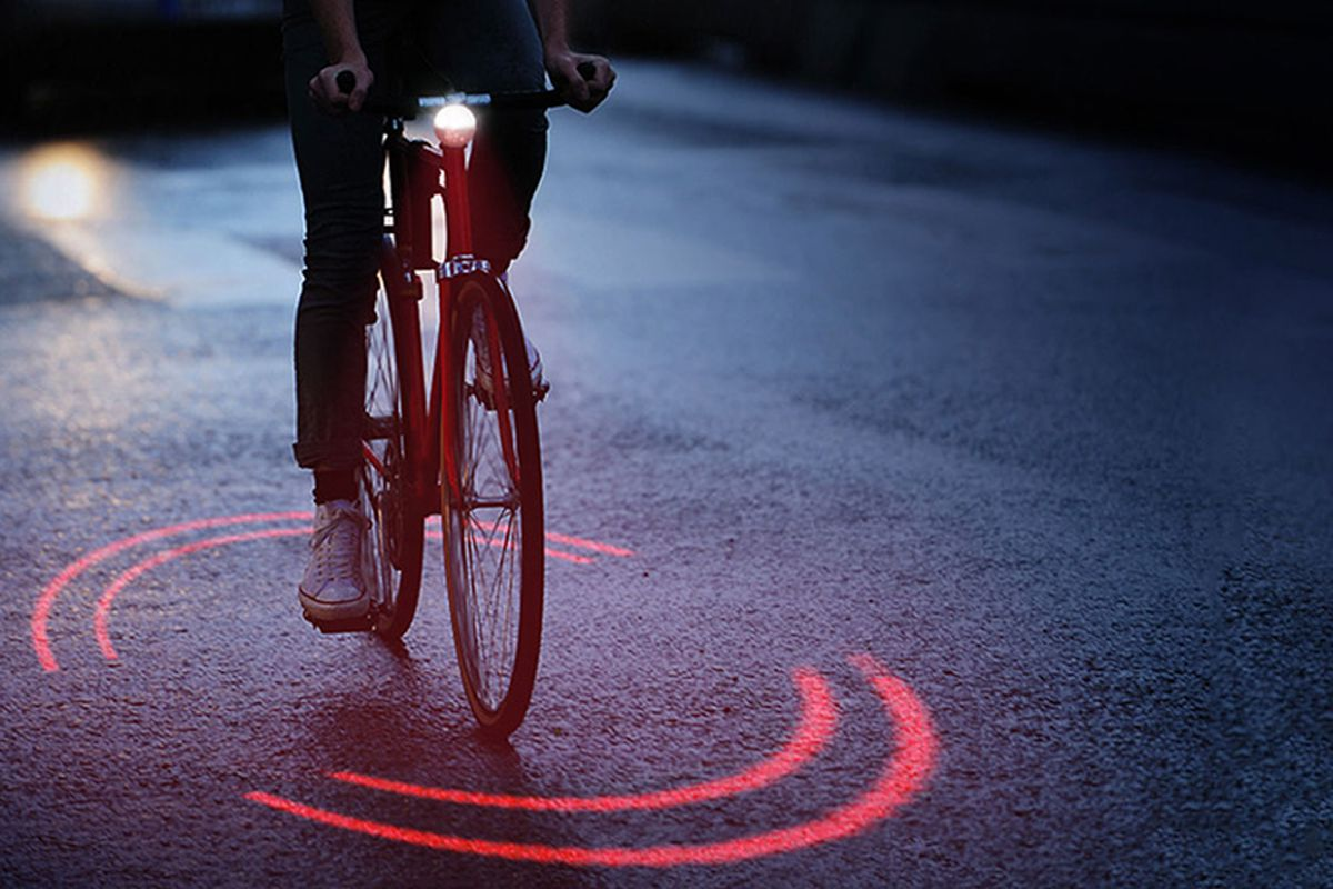Image of biker at night with ring of two red laser lights on the ground surrounding him.
