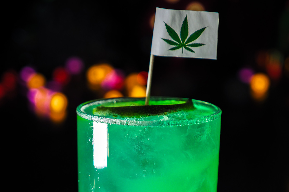 A green drink in a highball glass with a novelty marijuana leaf flag.