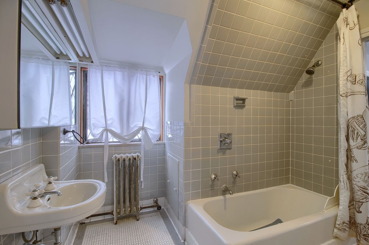 A small porcelain sink and bath tub. The walls are made of square gray tiles.
