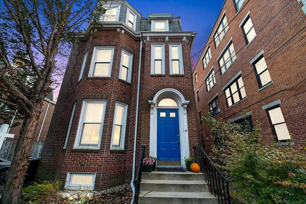 A narrow three-story townhouse with a pumpkin next to the closed front door.