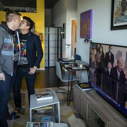 Matt Schreck, 43, and his husband, Fernando Gutierrez, 41, kiss as they watch the inauguration ceremony for President Joe Biden and Vice President Kamala Harris from their South Loop home, Wednesday morning, Jan. 20, 2021.
