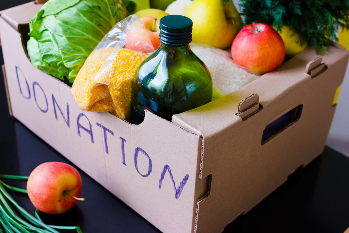"""A cardboard box marked """"Donation"""" filled with fruits, vegetables, and a bottle of cooking oil"""