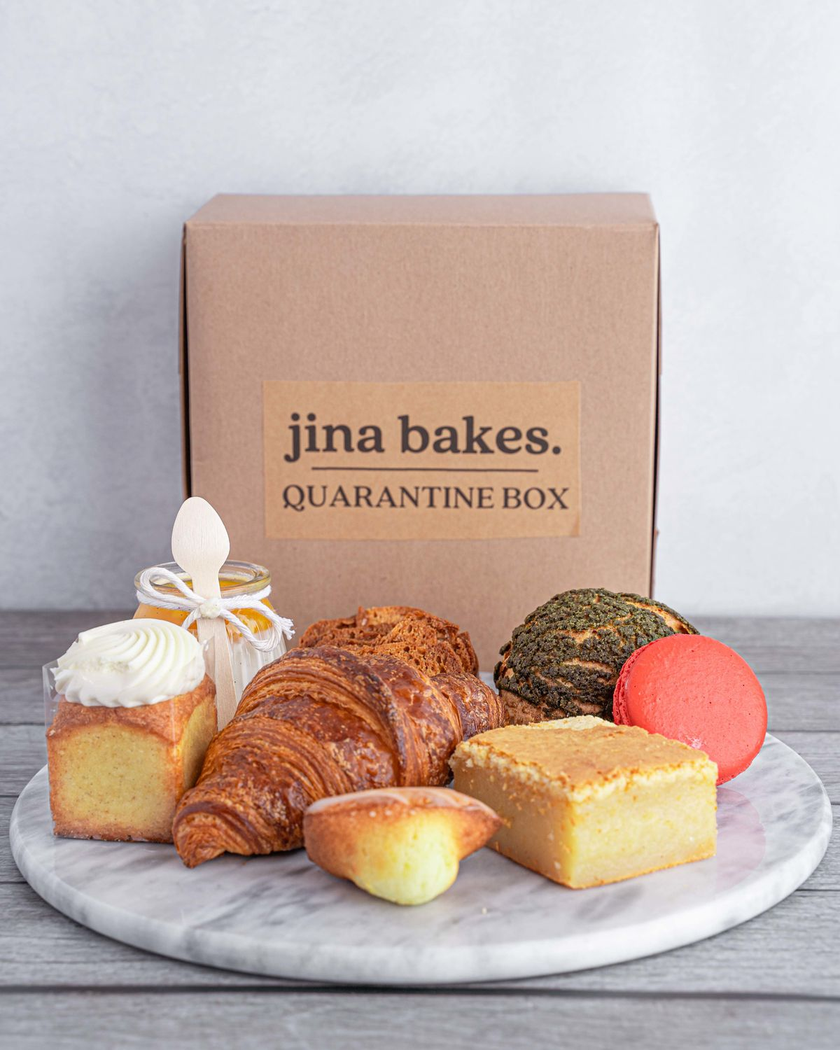 """Assorted pastries arranged in front of a Jina Bakes """"Quarantine Box"""""""