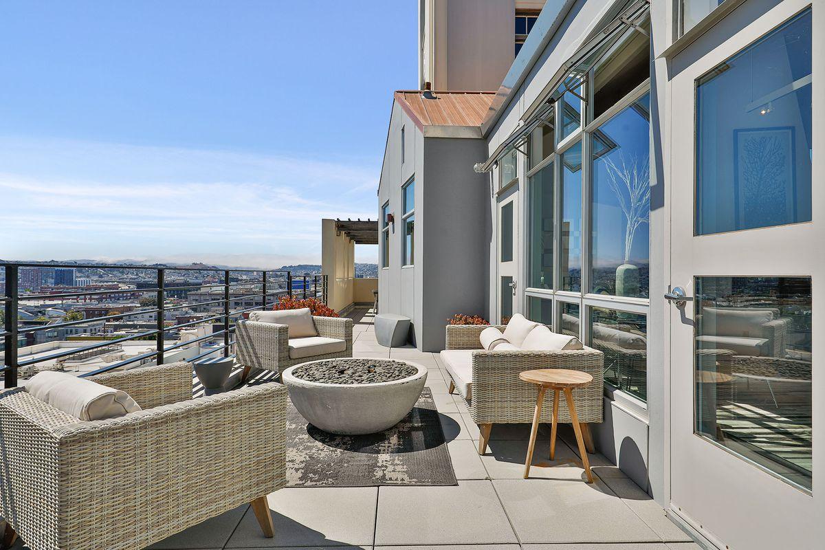 An outdoor patio with wicker chairs, overlooking flat buildings below.