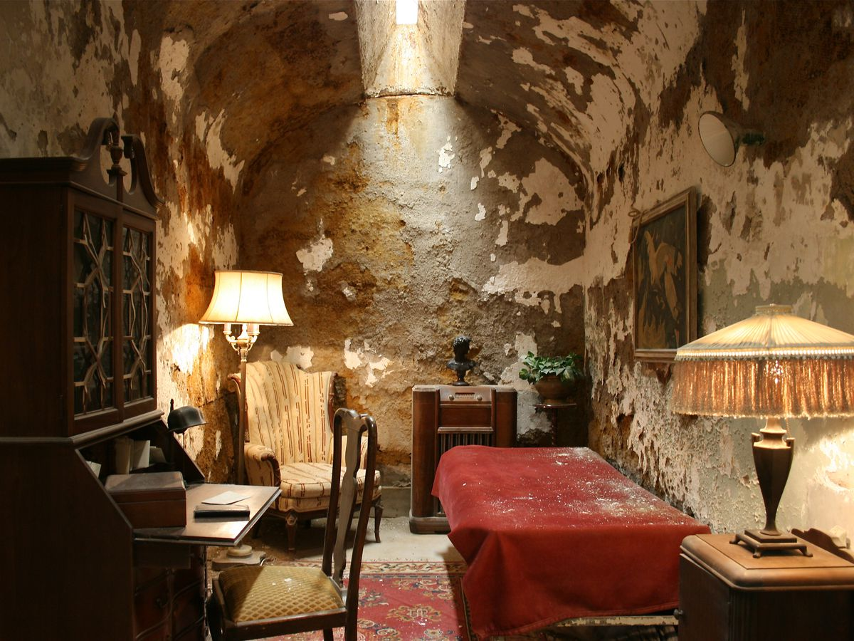 A room in the Eastern State Pentitentiary. The walls have decayed peeling paint. There is a bed, desk, chair, table, and lamp with a fringed lampshade.