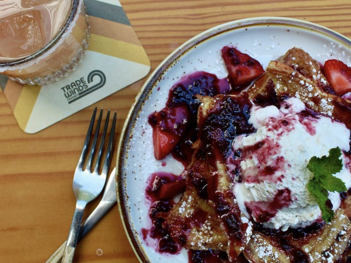 A topdown view of French toast with berry compote next to a cocktail on a wood table with a retro coaster that says Trade Winds Tavern.