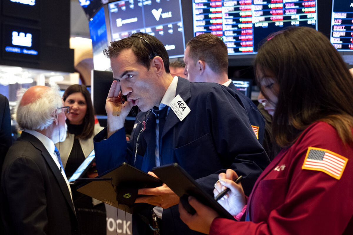 Trader Gregory Rowe, center, and others work on the floor of the New York Stock Exchange