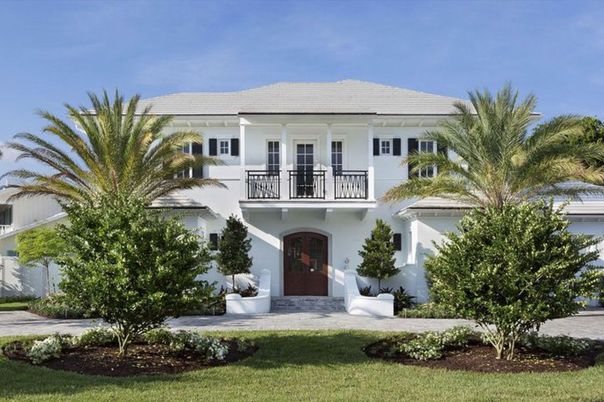A white home in Delray Beach with nicely manicured grounds