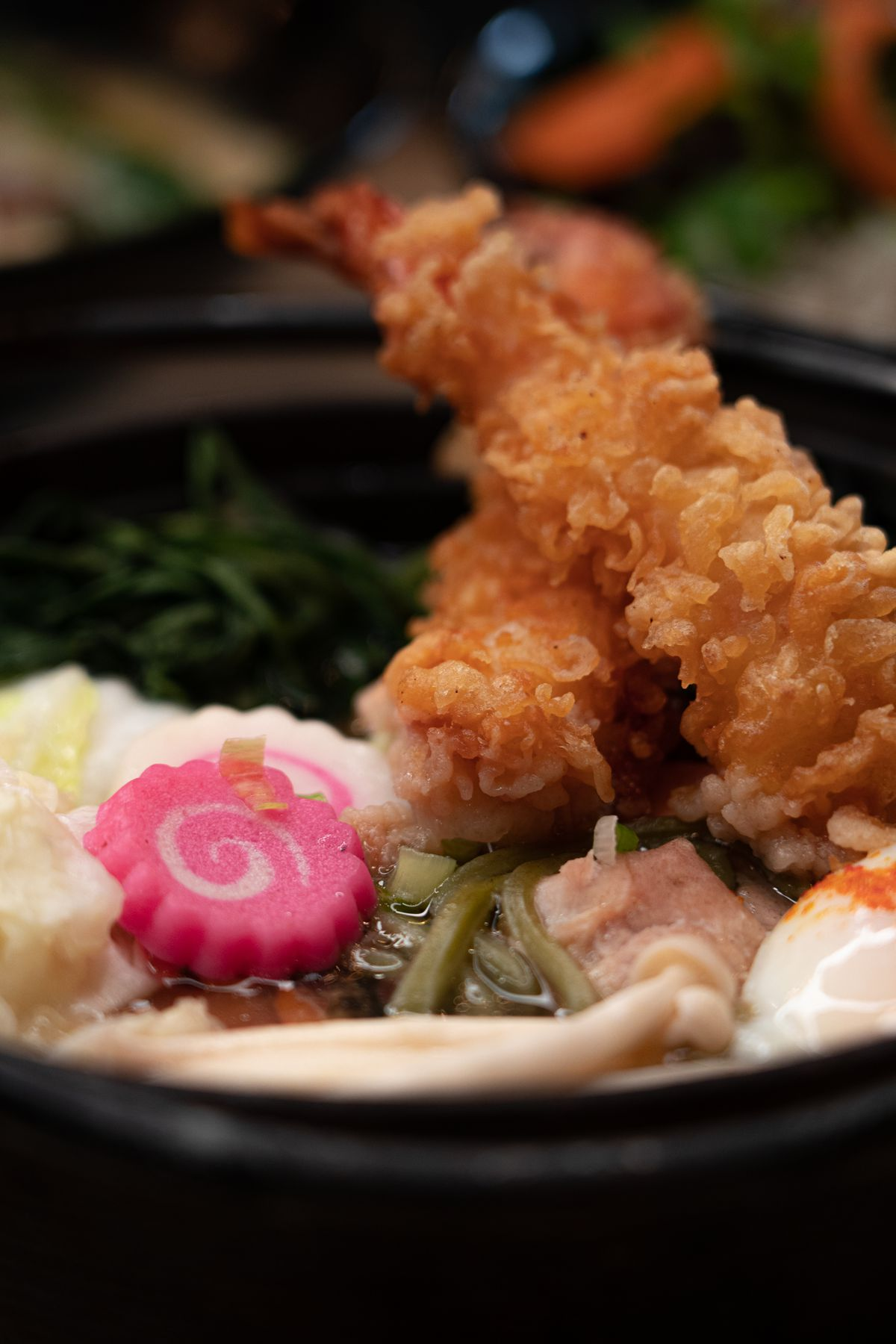 A close-up photograph of two crispy pieces of tempura, which sit atop a bowl of broth, greens, and other ingredients
