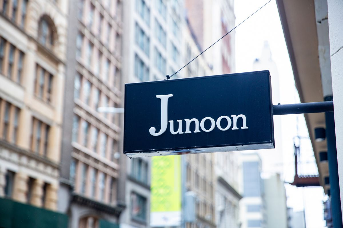 """A navy blue sign with the word """"Junoon"""" in white font stands against a city backdrop"""
