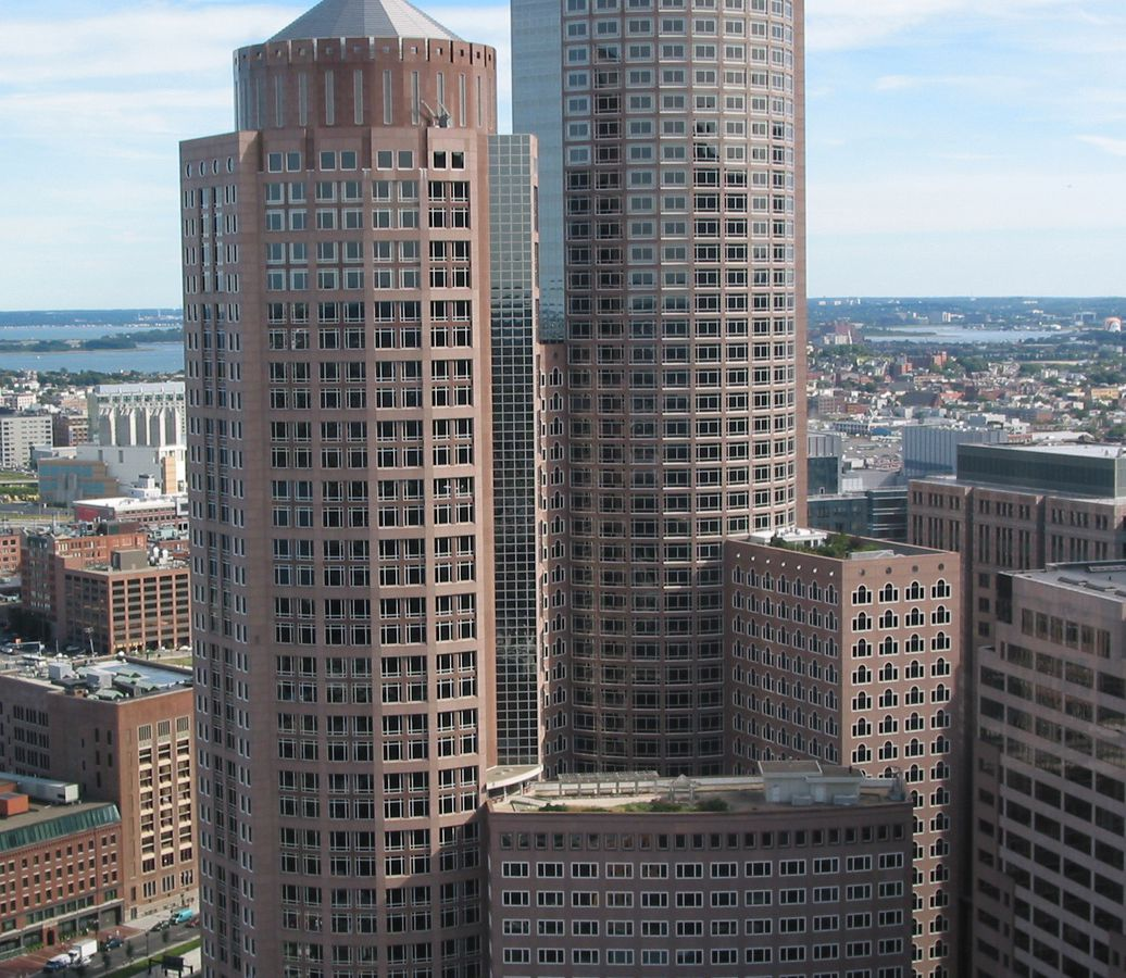 In the foreground is One International Place in Boston. The building is tall with many windows and red brick.