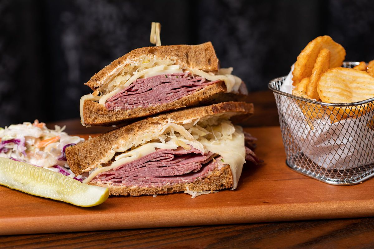 a rueben sandwich and cup of fried potatoes on a wooden bar