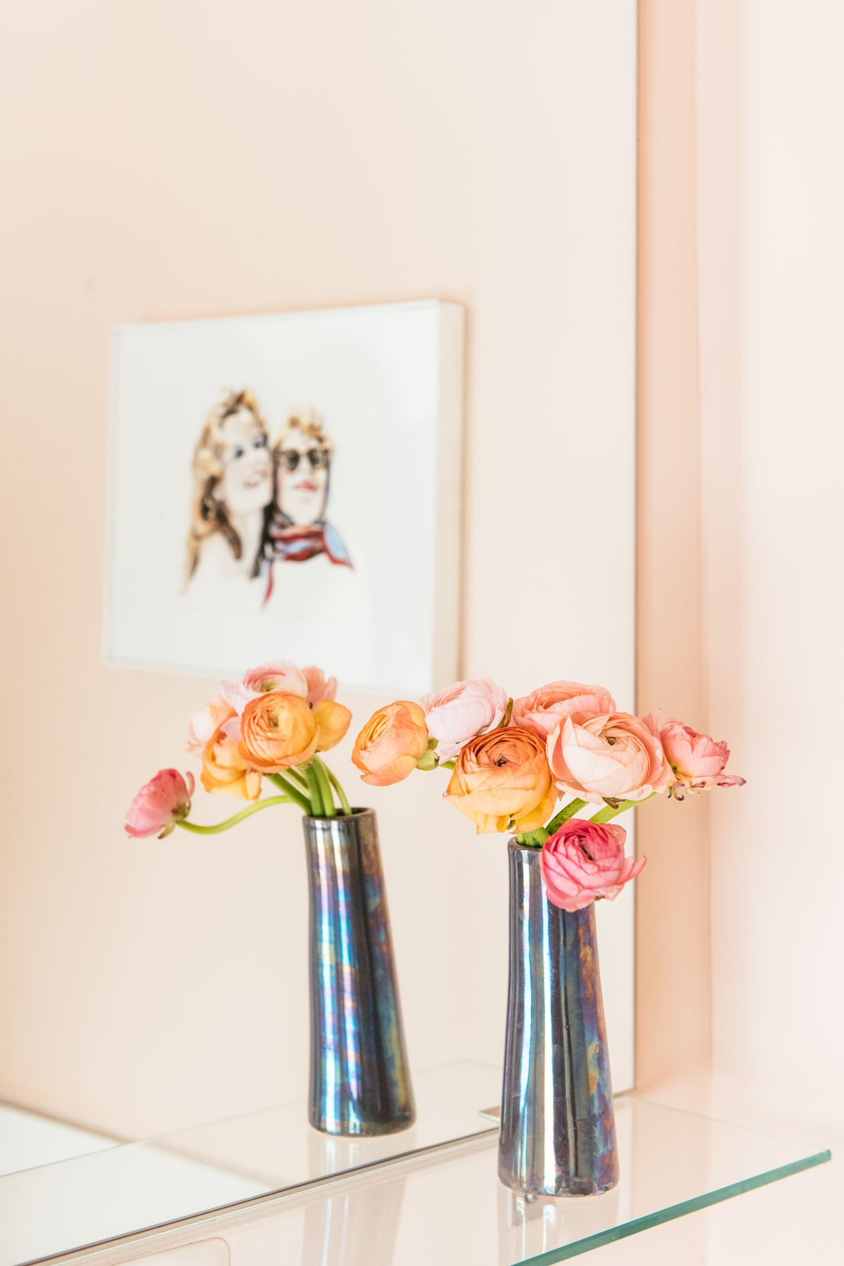 A shelf in the bathroom. There is a glass shelf with a metallic silver vase which holds colorful flowers. There is a mirror that shows a work of art hanging on the wall in its reflection.