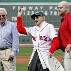 Bill Hogan Jr., center, throws out the ceremonial first pitch in celebration of his 100th birthday before a baseball game between the Boston Red Sox and the Tampa Bay Rays in Boston, Saturday, April 14, 2012. The Red Sox will celebrate the 100th anniversary of Fenway's opening when they host the New York Yankees on Friday.