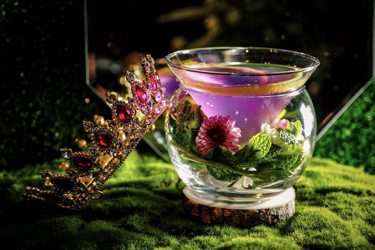 A pink cocktail in a glass surrounded by flowers and a crown.