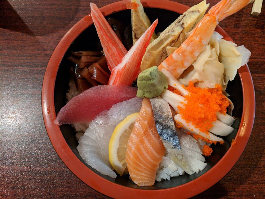 A red bowl of chirashi on a wooden table, filled with salmon, tuna, crab stick, shrimp, and other slices