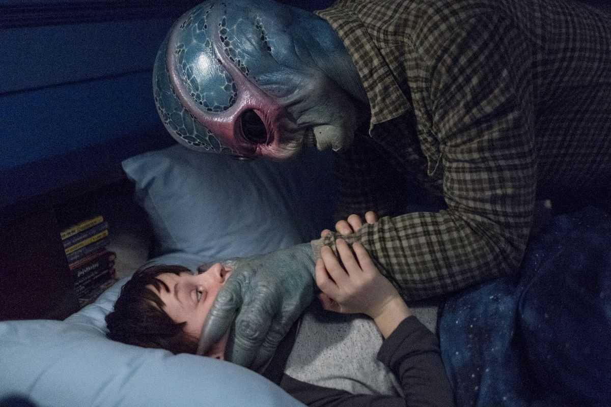 Alien Harry pins his child nemesis down with a three-fingered blue hand over his mouth in Resident Alien
