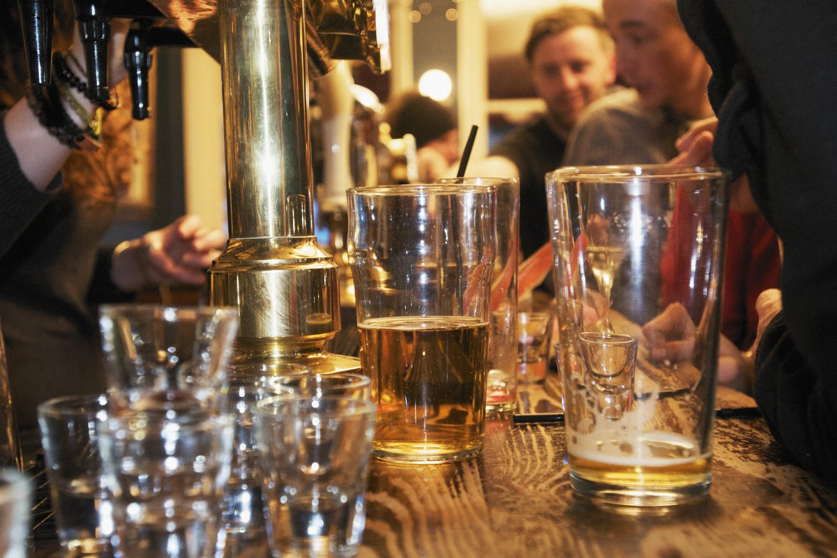 A close-up of several glasses on a bar, with patrons in the background.