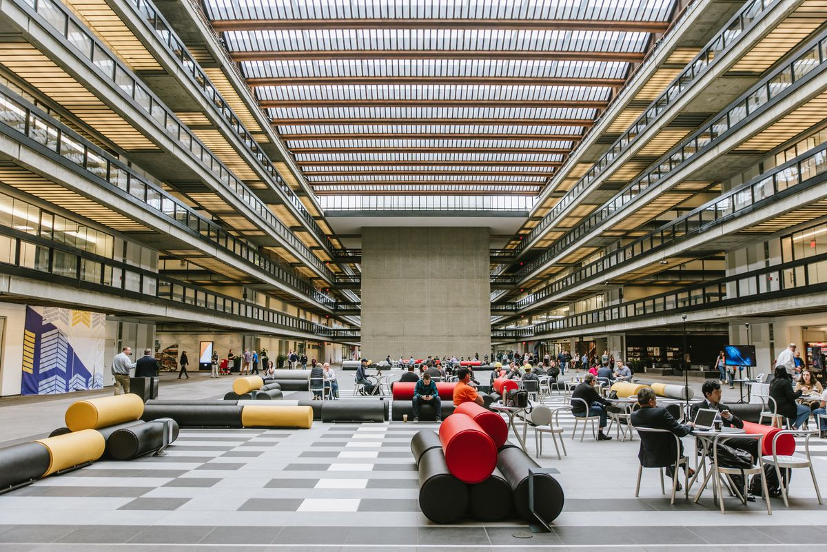 People work at tables in a mixed-use building that formerly housed a research and developmentfacility for Bell Labs.