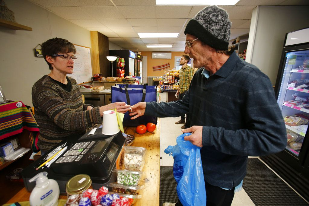 """Dianne Shenk, left, helps a customer Terry Warby in Dylamatos Market in Pittsburgh. """"These boxes will be full of shelf-stable items, the same things we're being told not to eat,"""" she said. (AP Photo/Gene J. Puskar)"""