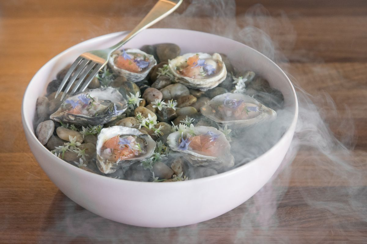 A closeup of oysters cooled with liquid nitrogen and garnished with grapefruit.