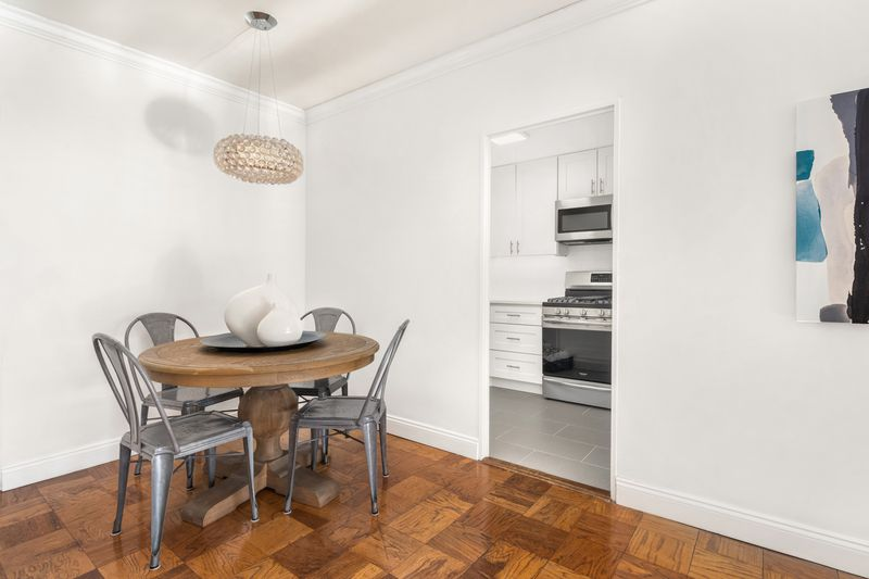 A dining area with hardwood floors, white walls, and a round dining table with four chairs.