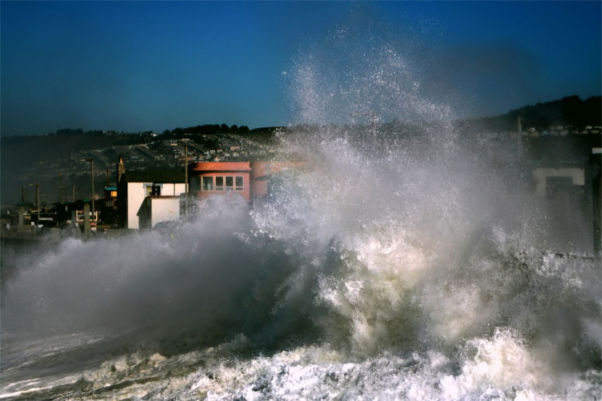 Large waves blocking the view of homes in Pacifica.