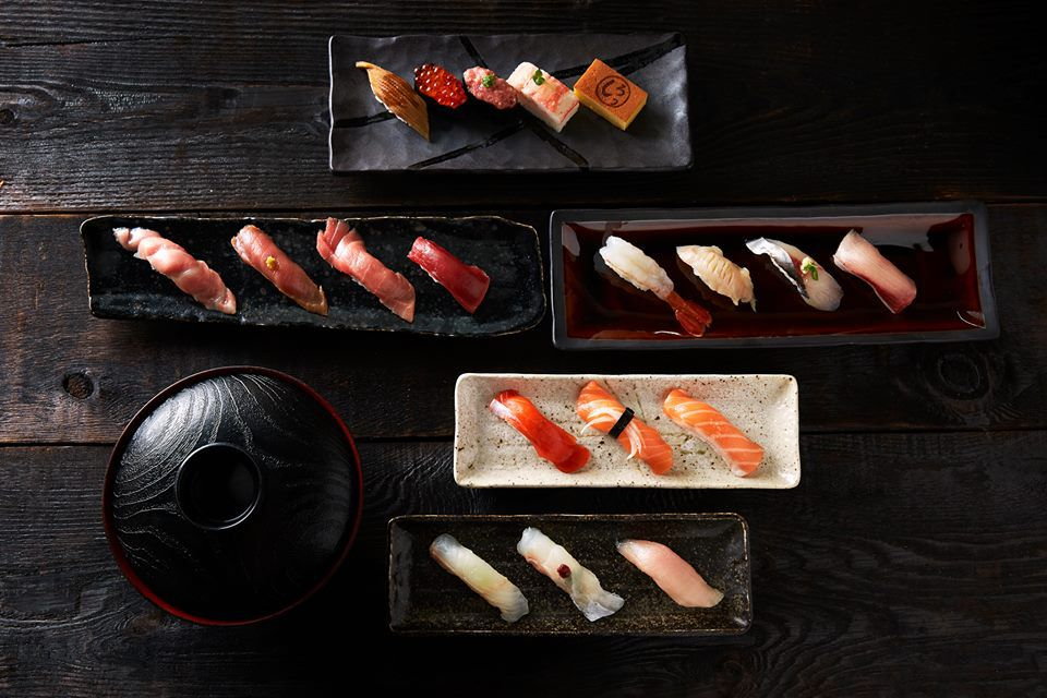 A top-down view of various nigiri against a dark background.