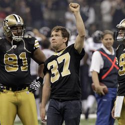 FILE - In this Sept. 25, 2011, file photo, former New Orleans Saints football player Steve Gleason raises his hand to the crowd as Saint quarterback Drew Brees (9) and defensive end Will Smith (91) look on. before the first start of NFL football game against the Houston Texans in New Orleans.  Gleason says he never authorized a documentary film maker to release an inflammatory recording of disgraced defensive coordinator Gregg Williams.