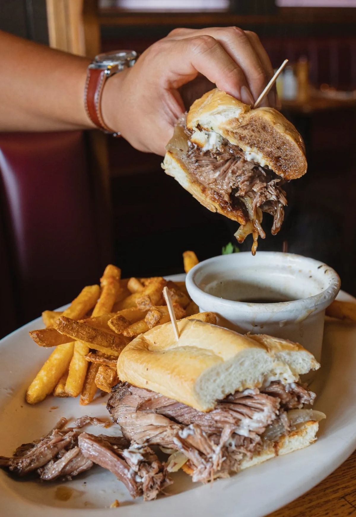 A hand dips a roast beef sandwich into juice.