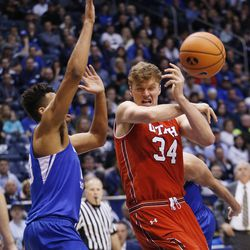 Utah Utes forward Jayce Johnson (34) is defended by Brigham Young Cougars forward Yoeli Childs (23) in Provo on Saturday, Dec. 16, 2017. BYU won 77-65.