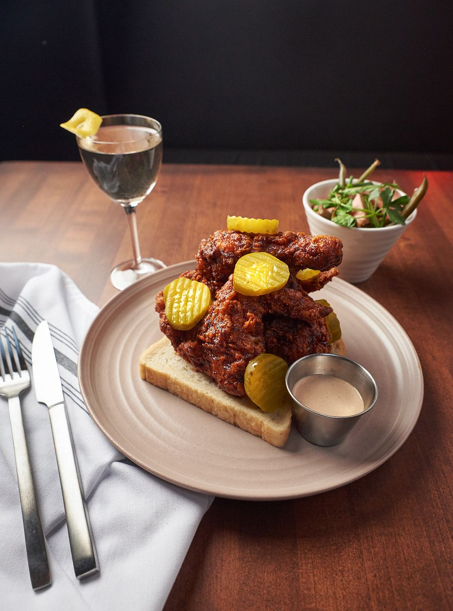 A wooden table with a plate of hot chicken and dark red wood and cocktail beyond.