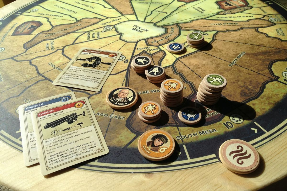 A map of Arakis, rendered in tan and brown tones, on a circle of wood. The chits and cards on top show a sandstorm approaching a massed battle between the Fremen and the Emperor's best while the Bene Gesserit look on.