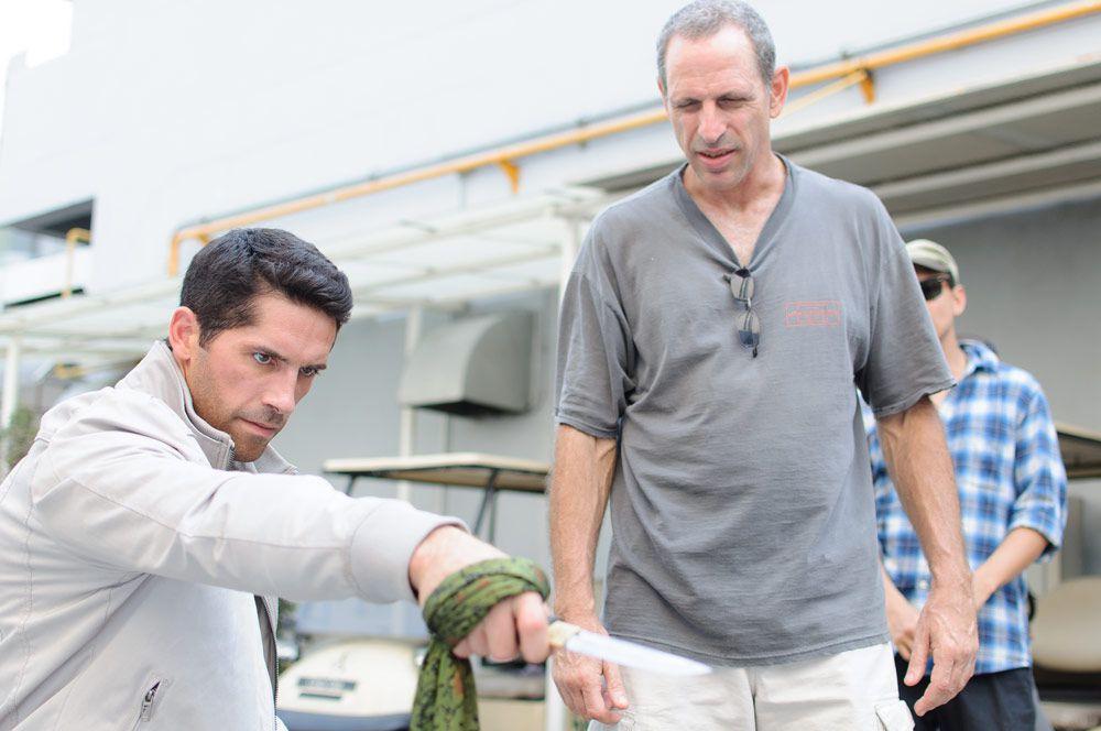 scott adkins practices using a knife alongside director isaac florentine