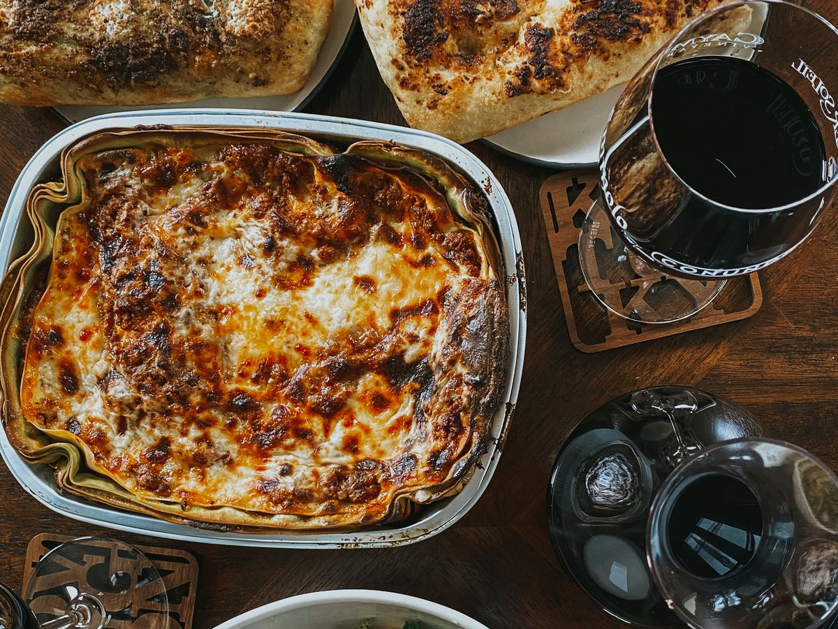 A tin dish of lasagne, along with plates of bread and salad, and glasses and a bottle of red wine