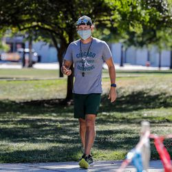 Lane cross-country coach Kris Roof times runners during practice on August 19, 2020.