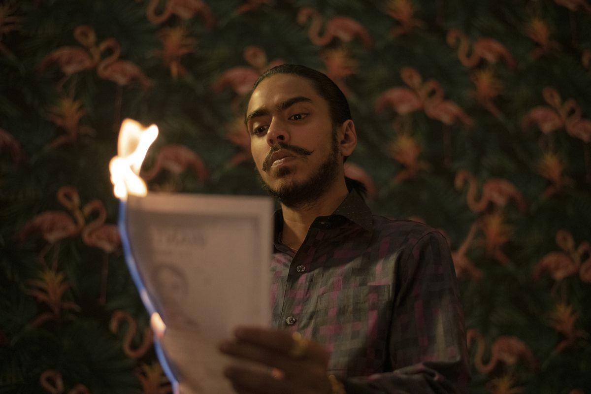 A young man sets fire to a stack of papers he is holding in his hand.