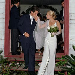 Aw shoot that's cute: John F. Kennedy, Jr. smooches Carolyn Bessette Kennedy hand while she wears a silk crepe gown by Narciso Rodriguez.