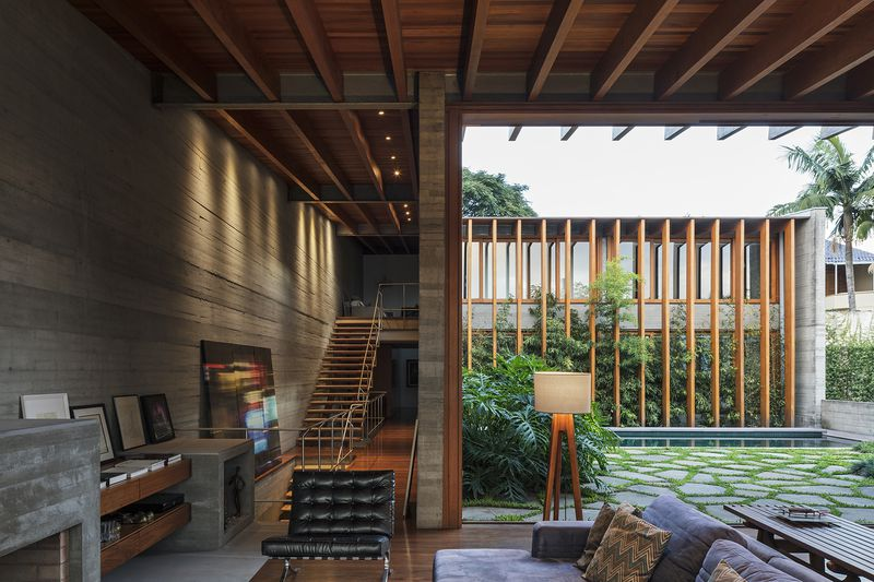 The living room opens onto garden adjacent to a large central staircase.