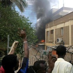 Sudanese protesters react as a fire rages during a protest outside the German embassy in Khartoum, Sudan, Friday, Sept. 14, 2012, as part of widespread anger across the Muslim world about a film ridiculing Islam's Prophet Muhammad. Germany's Foreign Minister says the country's embassy in the Sudanese capital of Khartoum has been stormed by protesters and set partially on fire. Minister Guido Westerwelle told reporters that the demonstrators are apparently protesting against an anti-Islam film produced in the United States that denigrates the Prophet Muhammad.