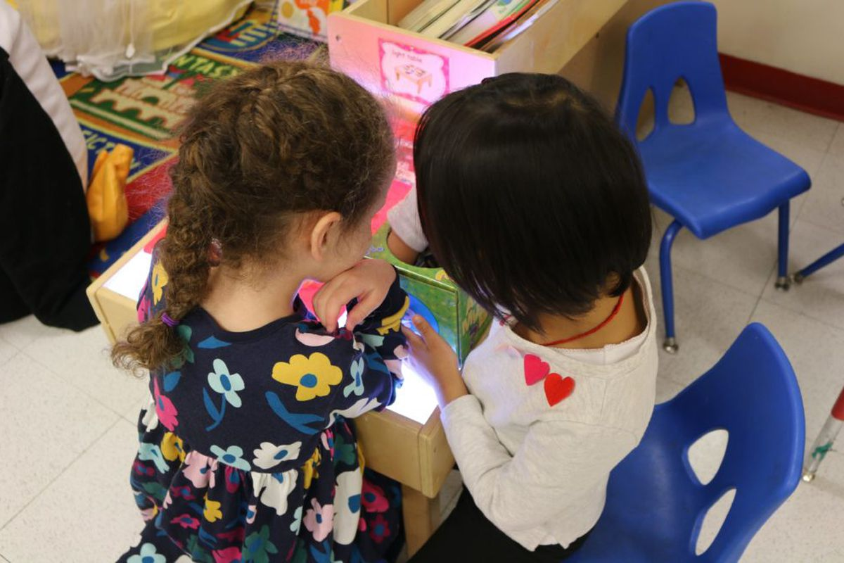 Pre-K students play at a light table at The Renaissance Charter School in Jackson Heights.