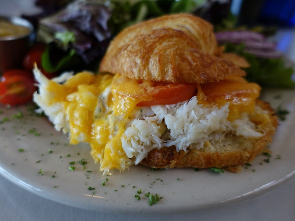 Crab sandwich on croissant with melted cheese and tomato on a plate.