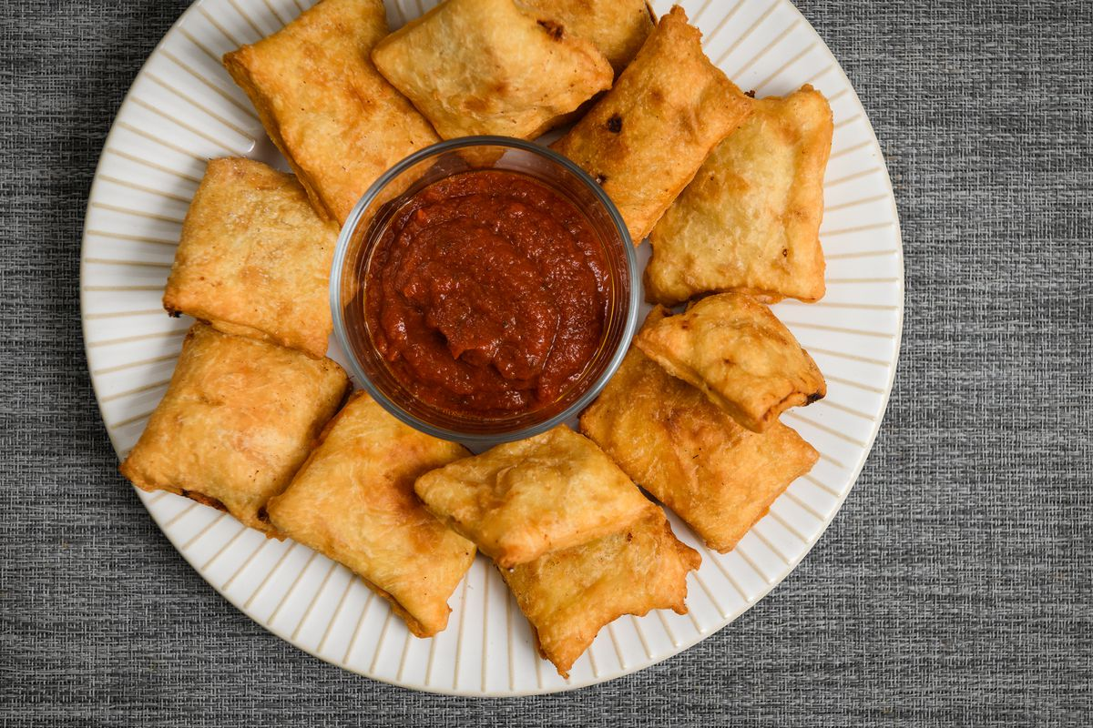 Homemade pizza rolls on a plate alongside a small dish of red dipping sauce.