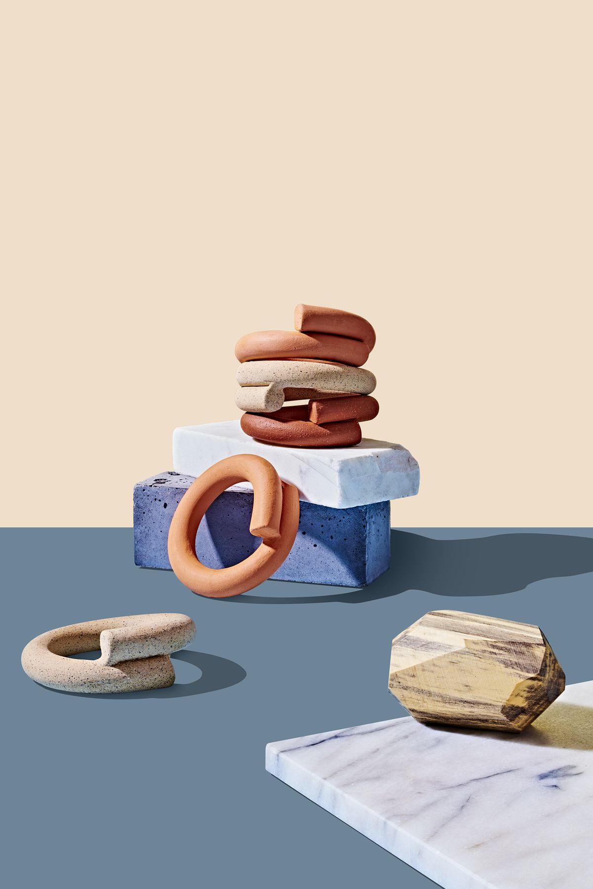 A group of earth toned handmade ceramic napkin rings stacked on top of each other. These are part of the 2019 Holiday Gift Guide for Curbed. The rings are sitting on design objects on a flat blue surface. There is an ivory colored backdrop.