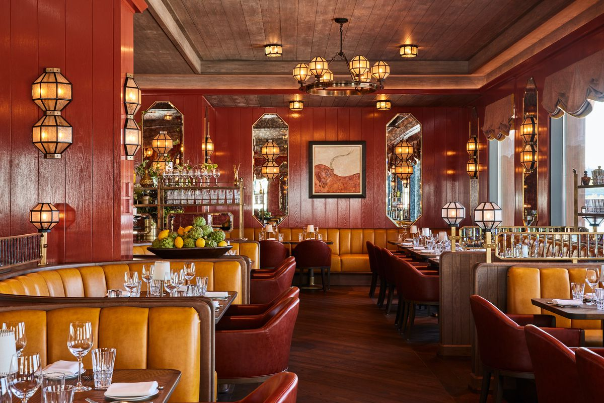 A luxe dining room with gold trim, red and orange booths, custom light fixtures, and fruit on display