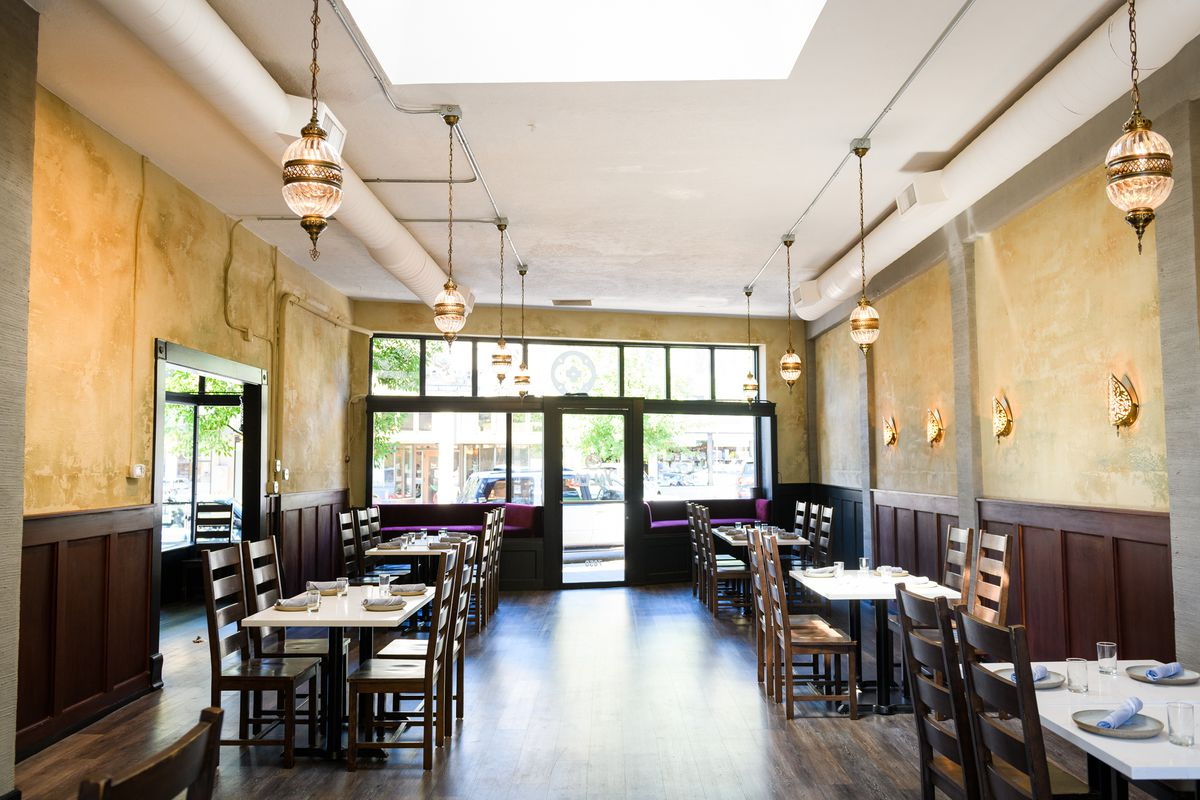 Wooden tables sit six feet apart on the wooden floors of Yalla, with white tabletops reflecting the light of the large windows.