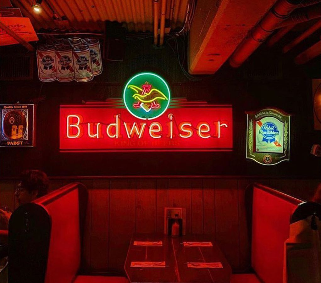A red-lit booth in a dark bar. A large neon Budweiser sign is on the wall behind it.